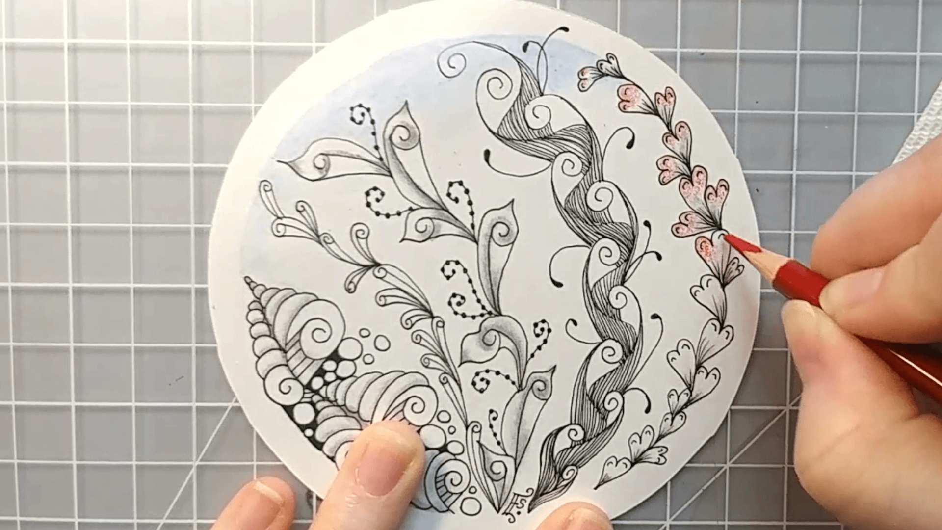 Zentangle inspired art tutorial using patterns with a swirl theme being hand drawn and colored with watercolor pencils