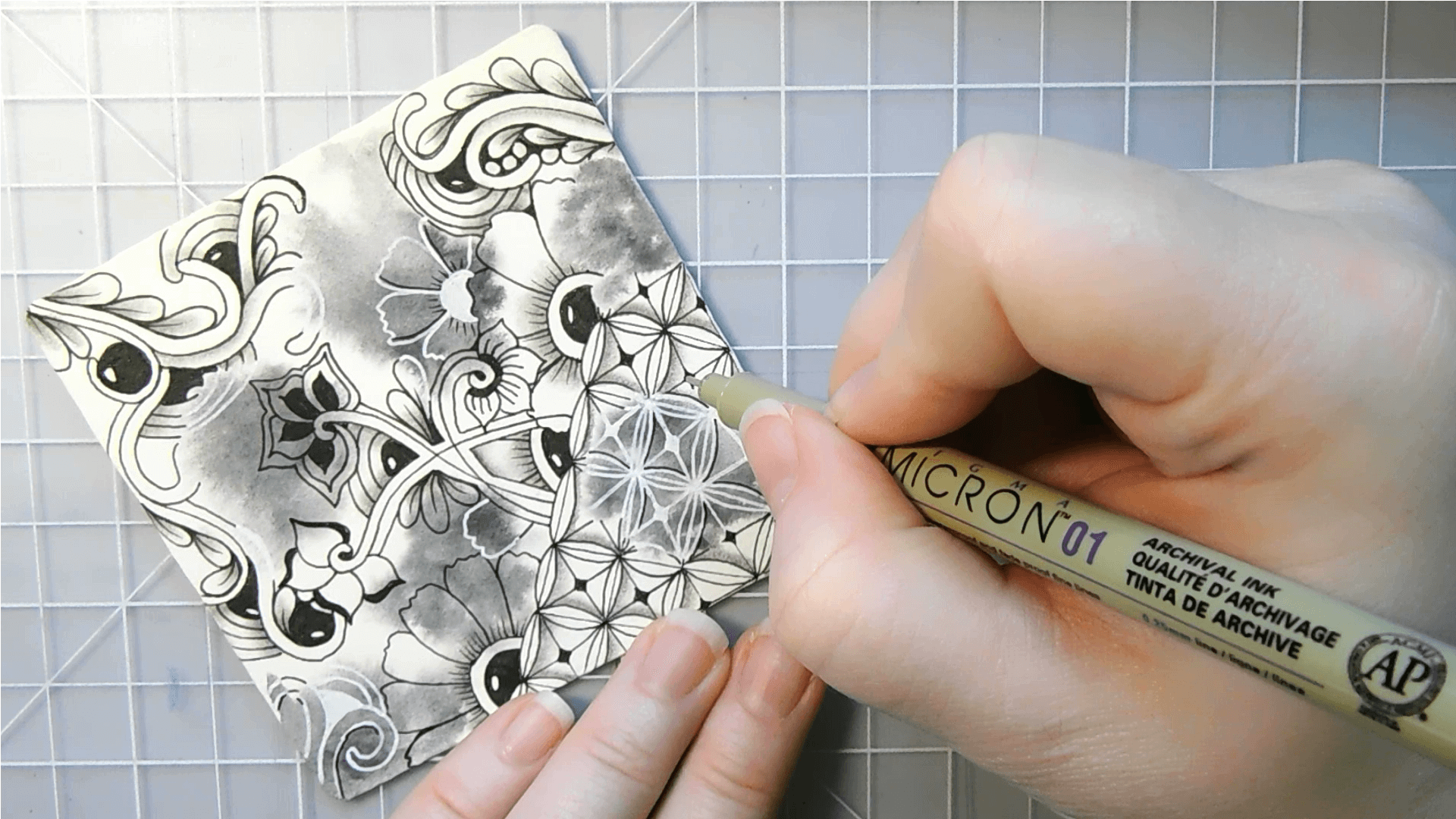 Zentangle with watercolor in black, white, and shades of gray on being drawn by hand on a cutting mat