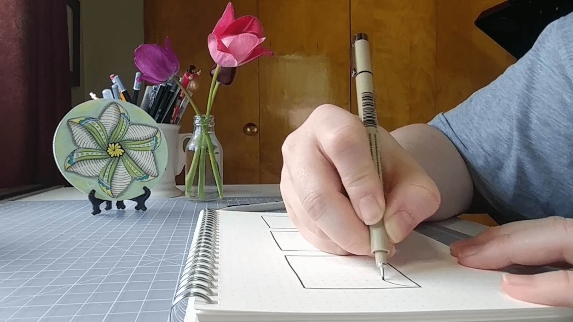 Emily Suess drawing Zentangles at her desk. There are tulips in a small glass vase and a Zentangle Zendala tile in the background.