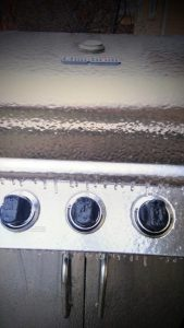 Metal gas grill covered in ice with knobs frozen in place and icicles hanging off of it.